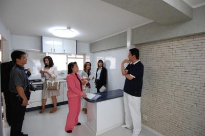 中野オーナーの話を聞く、日管協レディース委員会一行(オーナーの左は、北澤艶子委員長)。オーナーの後ろの壁(ダイニング部分)には、一面タイルが張りこまれている。メーカー工場へ直接赴き、安く仕入れた
