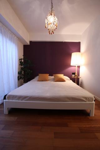寝室は温かみのあるボルドーのクロスを採用。暖色系の照明にも注目