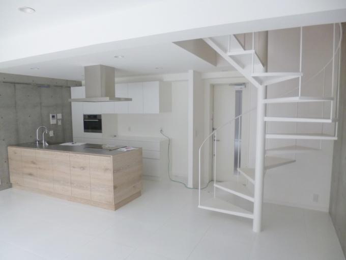 地階が1階になっているメゾネットタイプの部屋。壁はコンクリート打ちっぱなしで、白を基調としたシンプルな空間。キッチンはオーダーメイド