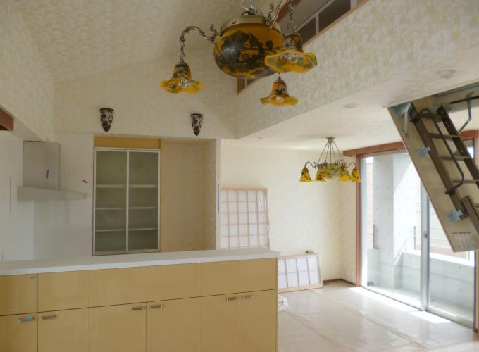 オレンジ色を基調にしたキッチン。壁紙や照明にもこだわりのデザインを採用。リビングの天井には、物置用のロフトが設けられている