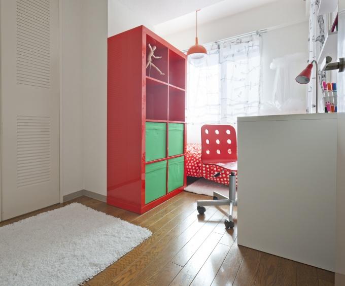 """""""小学生の女の子の部屋""""をテーマにインテリアコーディネートされた部屋。写真だとわかりづらいが、現地では梁と柱のでっぱりが相当気になった。そこで、柱に合わせて収納を置き、勉強机も置くことで、奥を「寝室」としてゾーニングするようなレイアウトに"""