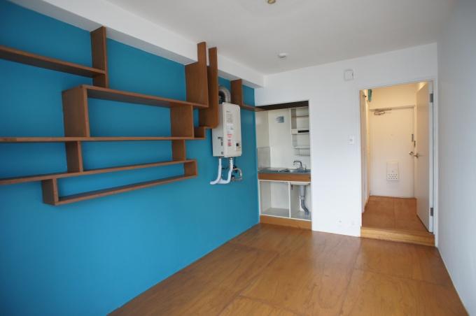 (有)ランドマークスの手掛けたオーダーメイド型物件の1室。青い壁紙の上に特徴的な吊り棚を設置(写真提供:ランドマークス)