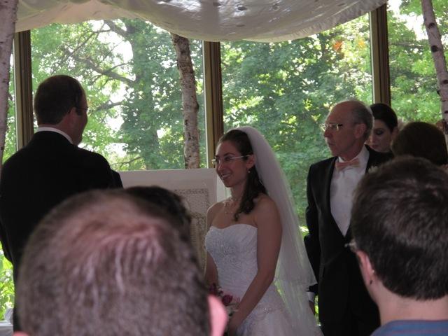 フッパの下で家族や友達に囲まれて律法師(花婿の後ろで見えないが)により祝福を受けるカップル