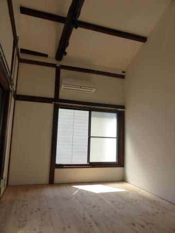 メゾネット2階部分。6畳半ながら高い天井や白の内装材と木材で統一された空間によって、広く感じられる