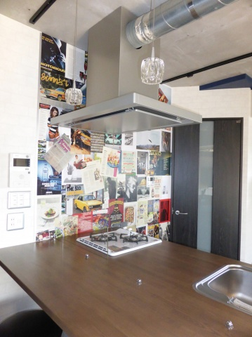 キッチンは、アイランド兼カウンターのような形に造作。壁は、作業に参加した大家仲間と共に、英字雑誌の切り抜きなどを貼り付けて仕上げたそう