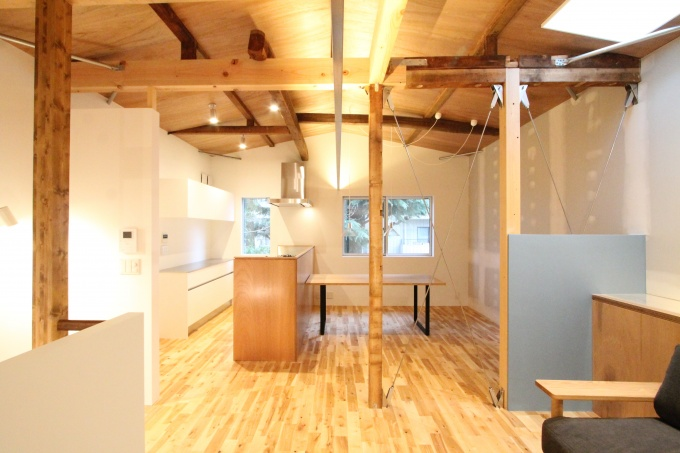 住居部分はシンプルな2LDK。柱を旧物件のもの、床材を無垢の端材を利用することで味わいを出した。一部を吹き抜けにすることで1階まで採光を上げている