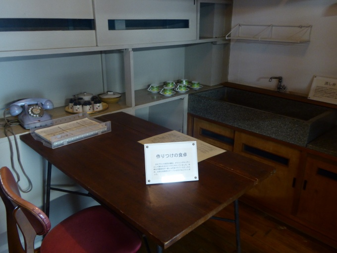 「蓮根団地」のDK。同団地では徐々にステンレスキッチンが導入されていったが、復元住戸はその前の人研ぎ流し台のもの。ダイニングテーブルは造り付け