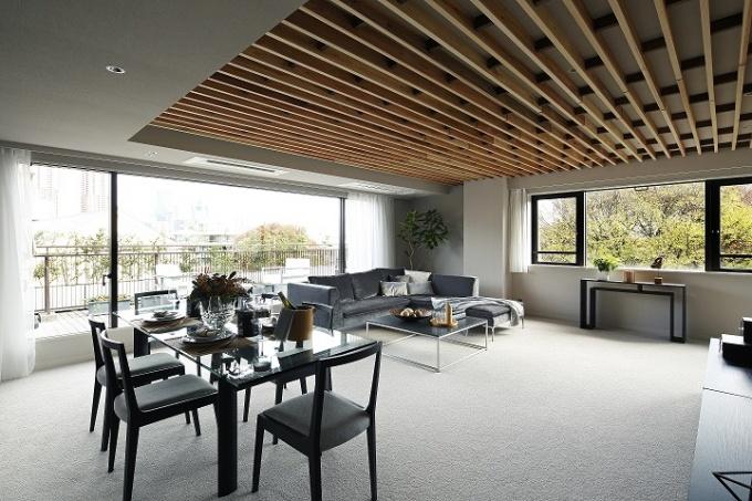 デザイナーによってつくり込まれた(オーダーメイド)タイプのモデルルーム。室内空間はシンプルでありながら上質感を演出。リビングの天井は吉野杉のルーバーで仕上げ、アクセントとした(専有面積145.73平方メートル、間取り3LDK+WIC+RoofBalcony、販売価格は3億5,800万円。写真提供:(株)リビタ)