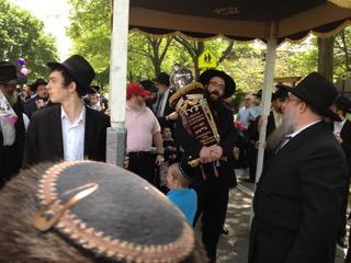 特別な祭礼の日、ユダヤ教の律法師は羊皮紙に書かれた巻物(トーラ)をかかえている(イリノイ州シカゴ市)