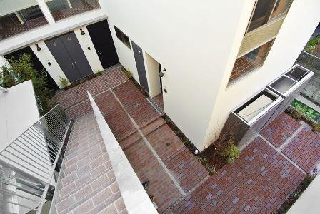 中庭にレンガを敷き詰め、さらに各住戸の洗濯物干場・自転車置き場として用意した「土間」「インナーテラス」もレンガ敷として、中庭と室内を連続した空間として見せている
