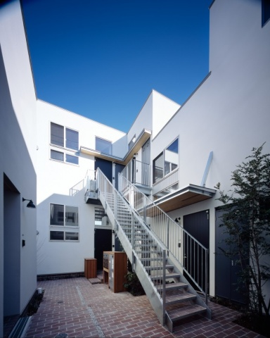 配棟上の最大のウリが「中庭」。住戸への通路を兼ねた中庭にはレンガが敷き詰められ、入居者のコミュニティスペースに。共同住宅の通路には屋根を設けなければならないが、建物用途をメゾネットと共同住宅とに分けることで屋根を付けず、空の見える中庭を実現した