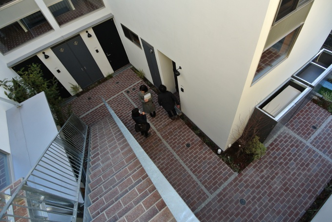 2階のワンルーム玄関から中庭を見る。階段もレンガ貼り。メゾネット住戸のサンルーム窓からのぞくレンガ床と、中庭のレンガが連続した空間となっている