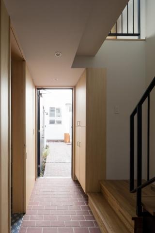 メゾネットも玄関部分はレンガ貼りの土間スペース。開け放つと、中庭と連続した空間のようだ